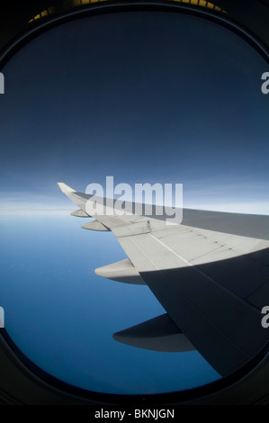 View from porthole of Boeing B747-400P wing and land, Malaysia - Stock Photo