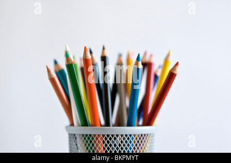 Colored art pencils in pencil holder, on white background. - Stock Photo