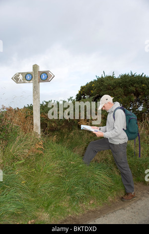Walker studying a map on the Anglesey Coastal Path by Red Wharf Bay, North Wales - Stock Photo