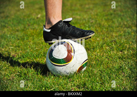 A close up view of a male soccer player's foot on a soccer ball - Stock Photo