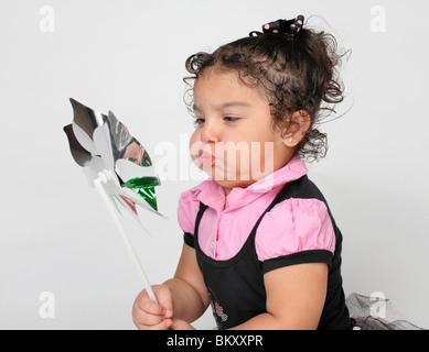 cute little Hispanic girl playing with a toy pinwheel in studio - Stock Photo