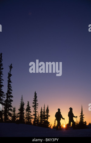 Couple snowshoeing during a colorful sunset in Mt. Rainier National Park, Washington. - Stock Photo