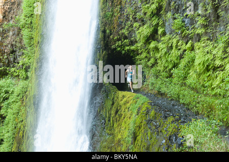 A woman running along trail blasted into a hill behind a waterfall on the Pacific Crest Trail, Oregon. - Stock Photo