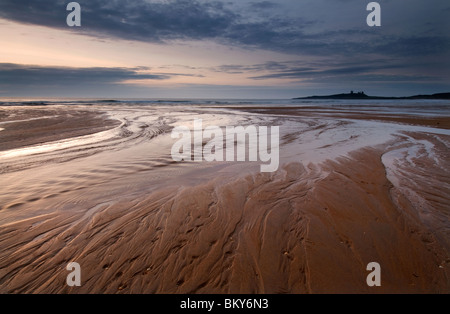 Dawn breaking over Dunstanburgh Castle from Embleton Bay - Stock Photo