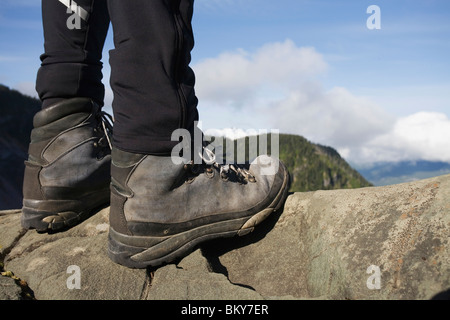 A low shot of a backpacker's lower legs and boots, standing on granite with forested mountains in the background. - Stock Photo