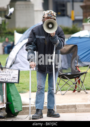 Brian Haw berates politicians from the Peace Camp in Parliament Square as they enter and leave the Houses of Parliament - Stock Photo