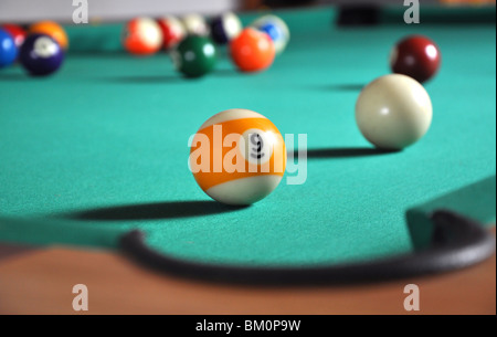 Billiard ball near hole, a lot of balls in blurry background - Stock Photo