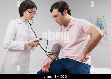 Female doctor checking man's blood pressure - Stock Photo
