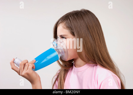 Girl using an asthma inhaler attached with a spacer - Stock Photo