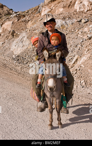 Man with twins on donkey in the mountains near Sary Tash, Kyrgyzstan - Stock Photo