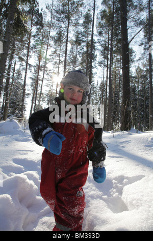 Baby toddler boy walks walking path track through snow covered forest near Godby on land Aland archipelago Finland - Stock Photo