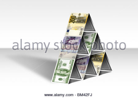 Stack of cards built in a triangle with twenty pound sterling, two hundred euro, and 100 dollar banknotes on the - Stock Photo