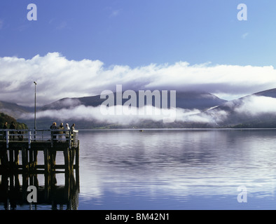 Inveraray, Argyll and Bute, Scotland, UK, People on the pier in Loch Fyne on calm autumn morning with low cloud - Stock Photo