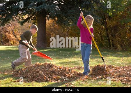 Children raking Autumn leaves - Stock Photo