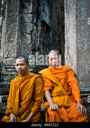 Two monks sit down at Bayon, Angkor Thom, one of the temples of Angkor in Cambodia - Stock Photo