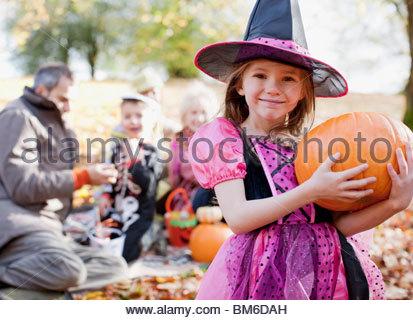 Girl in Halloween costumes holding pumpkin - Stock Photo