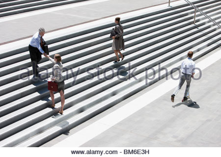 Business people shaking hands on steps outdoors - Stock Photo
