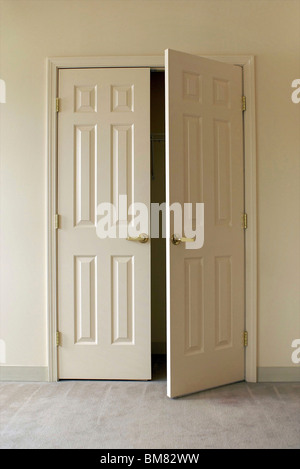 white closet doors, one open in an empty room - Stock Photo