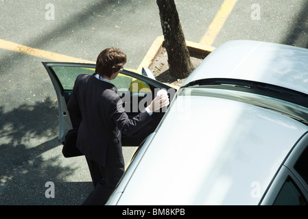 Businessman getting into car - Stock Photo