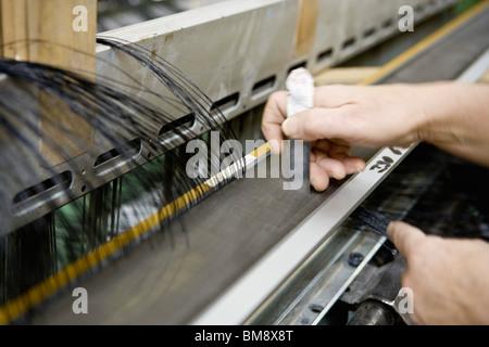 Fabric coating plant, weaving department, mechanist preparing weaver's reed on loom - Stock Photo
