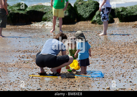 mother and two young boys with buckets at beach sea edge - Stock Photo