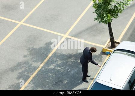 Businessman unlocking car door - Stock Photo
