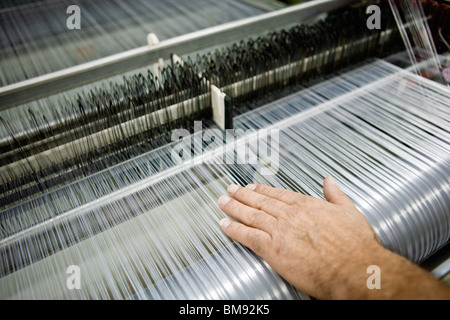 Weaving mill, machinist manually checking thread tension on a loom - Stock Photo