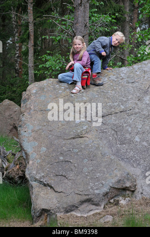 Young girl and boy sitting on a rock in Groenaasen forest near Kosta, Jonkopings Lan, Sweden - Stock Photo