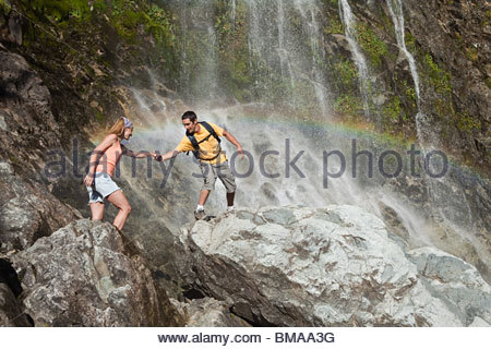 Couple on rocks by waterfall - Stock Photo