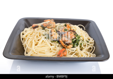 typical italian cooking: spaghetti with mussels and garlic. Plate isolated on white background with clipping path - Stock Photo