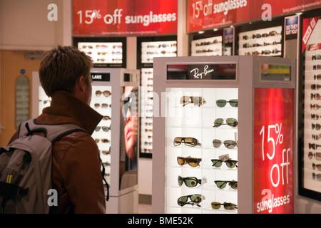 A man buying sunglasses, Terminal 3, Heathrow airport, London UK - Stock Photo