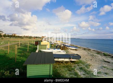 Beach huts and fishing boats on beach - Stock Photo
