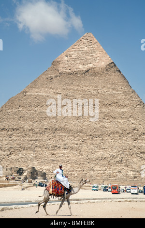 A lone rider guides his camel past the Pyramid of Khafre (Chephren), Giza, Cairo, Egypt - Stock Photo