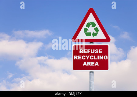 Signpost with text saying Refuse Recycling Area and a generic green recycling symbol against a blue cloudy sky. - Stock Photo