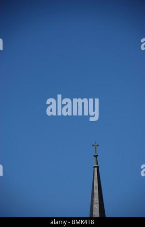 Church steeple with cross against blue sky. - Stock Photo