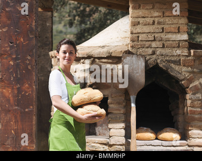 Woman holding freshly made bread loaves - Stock Photo