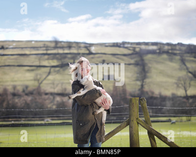 Woman holding lamb in front of fence - Stock Photo