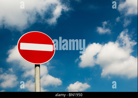 No entry road signpost against a cloudy blue sky. UK - Stock Photo