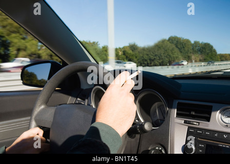 Smoking a cigarette while driving - Stock Photo
