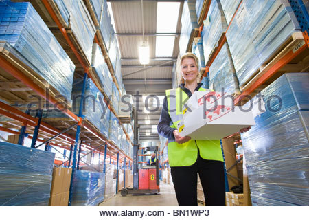 Portrait of smiling warehouse worker holding boxes in warehouse - Stock Photo