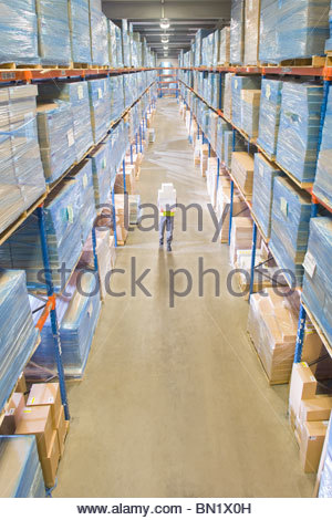 Warehouse worker carrying boxes in aisle - Stock Photo