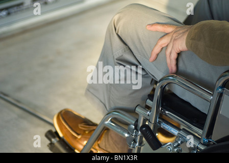 Handicapped person in wheelchair sitting outdoors - Stock Photo