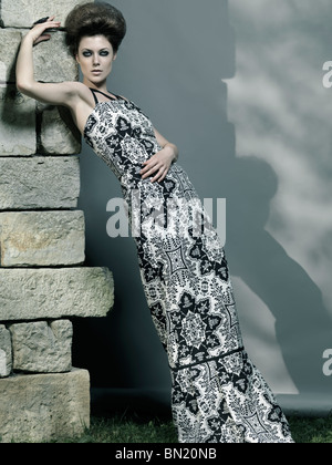 High fashion photo of a beautiful woman wearing elegant long dress - Stock Photo