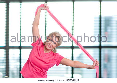 Portrait of smiling senior woman stretching with resistance band overhead - Stock Photo