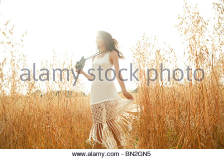 Woman standing in grass with camera - Stock Photo