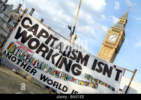 Parliament Square Peace Camp and Big Ben with anti Capitalism demonstration banner, Capitalism isn't working, London, - Stock Photo