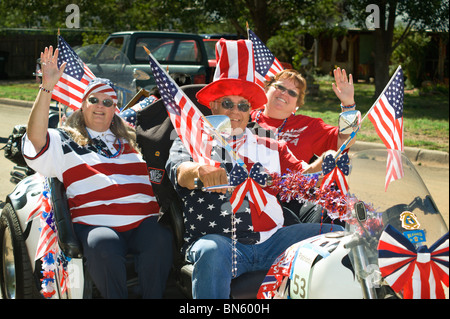 Parade participants wave at the 4th of July parade in Capitan, New Mexico. - Stock Photo