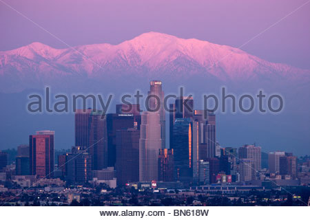 L.A. Skyline with Sunset Alpenglow on Snowy Mount Baldy Peak in Background, Southern California - Stock Photo