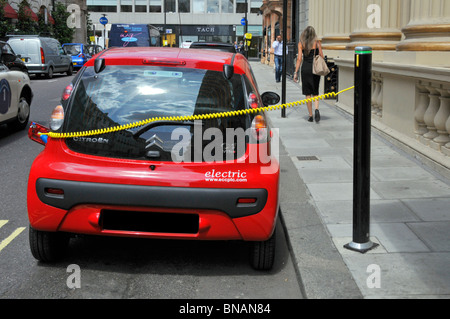 Electric car charging cable connects red Citroen car to electric car charging station or juice point provided by - Stock Photo