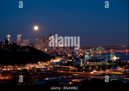 Moonrise from Magnolia Bluff Seattle Skyline at twilight with Space Needle and Port of Seattle Seattle Washington - Stock Photo